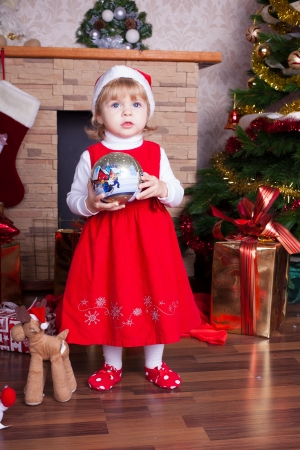 Beautiful blond little girl in a red Christmas hat posing by the fireplace on Christmas Eve, enjoys gifts  A series of photos in my portfolio Stock Photo - 16292585