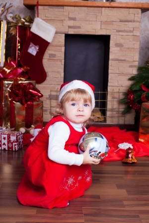 Beautiful blond little girl in a red Christmas hat posing by the fireplace on Christmas Eve, enjoys gifts  A series of photos in my portfolio  Stock Photo - 16292470