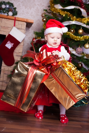 Beautiful blond little girl in a red Christmas hat posing by the fireplace on Christmas Eve, enjoys gifts  A series of photos in my portfolio Stock Photo - 16292591