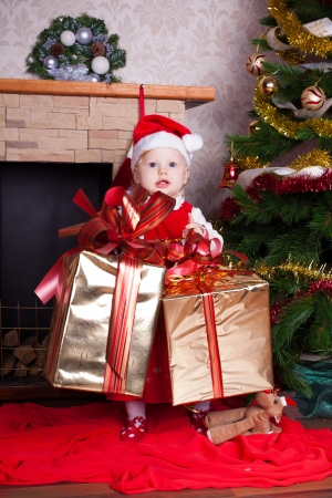 Beautiful blond little girl in a red Christmas hat posing by the fireplace on Christmas Eve, enjoys gifts  A series of photos in my portfolio Stock Photo - 16292531
