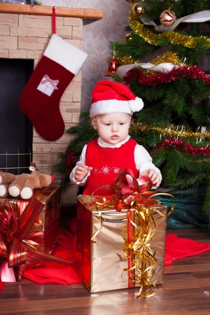 Beautiful blond little girl in a red Christmas hat posing by the fireplace on Christmas Eve, enjoys gifts  A series of photos in my portfolio  Stock Photo - 16292522