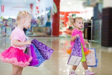Elegant little girls in a big shopping center posing on the background shop windows