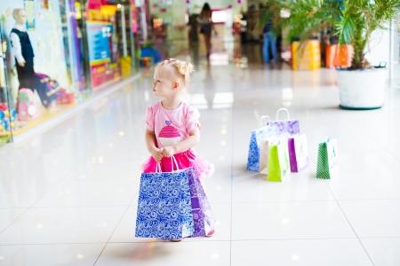 centro comercial: Elegante chica poco en un gran centro comercial que presenta en el fondo escaparates