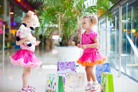 Elegant little girls in a big shopping center posing on the background shop windows   photo