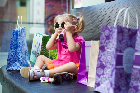 Elegant little girl posing on a big sofa in the mall on the background shop windows  photo