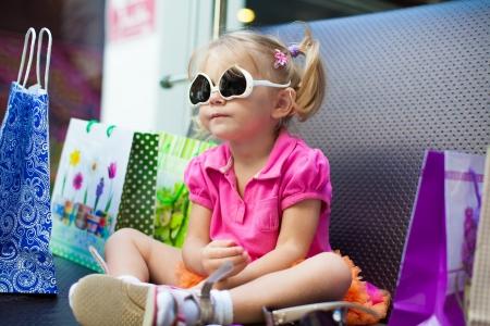 jolie petite fille: El�gante petite fille posant sur un grand canap� dans le centre commercial sur le fond des vitrines