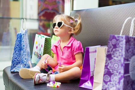 Elegant little girl posing on a big sofa in the mall on the background shop windows