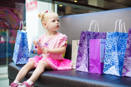 Elegant little girl posing on a big sofa in the mall on the background shop windows Stock Photo - 16291815