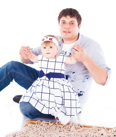 Young beautiful family Dad and little daughter posing in the studio on a white background  photo