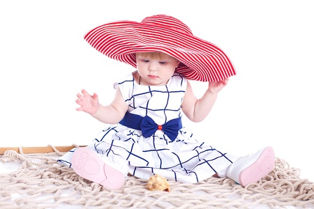 small beautiful child playing with a big red hat in the studio on a white background Stock Photo - 16302461