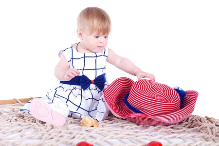 small beautiful child playing with a big red hat in the studio on a white background Stock Photo - 16302469