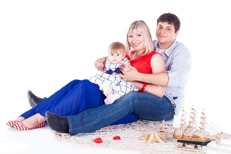 Young beautiful family of 3 persons Mum, Dad and little daughter posing in the studio on a white background  Stock Photo - 16302466