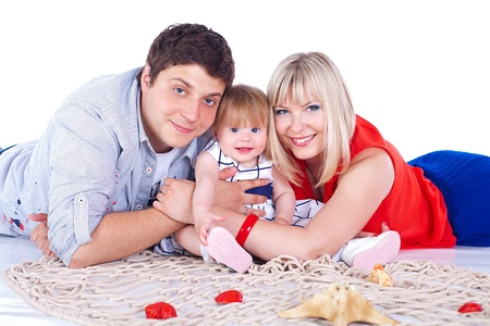 Young beautiful family of 3 persons Mum, Dad and little daughter posing in the studio on a white background  photo