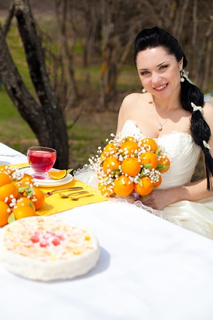 happy beautiful Bride at the banquet table in the countryside  Wedding Day, style in orange photo