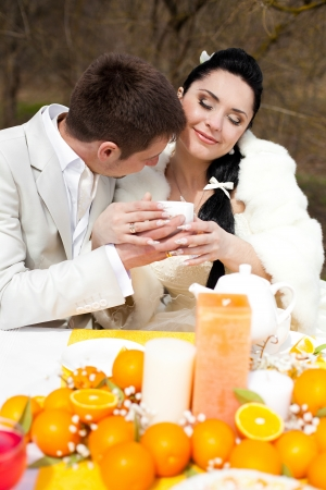 happy couple at the banquet table in the countryside  Wedding Day, style in orange photo