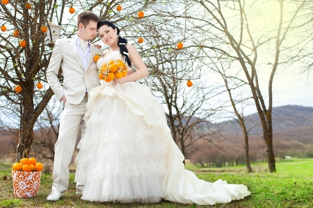 A beautiful pair of bride and groom posing in the park  Stylized Wedding in oranges  photo