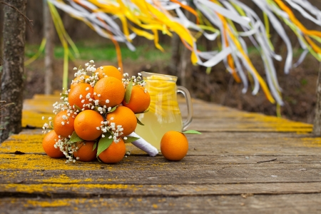 Stylized Brides Bouquet made of oranges lying on the bridge  Photo in the park on the lake