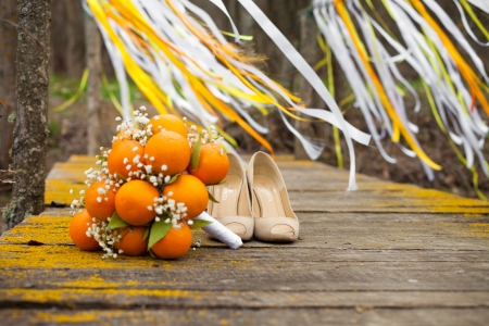 Stylized Brides Bouquet made ​​of oranges lying on the bridge  Photo in the park on the lake