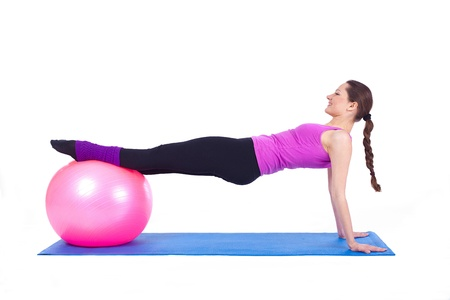 A healthy young woman exercising with fit-ball in gym   Stock Photo