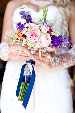 Bride holding beautiful wedding bouquet of purple and white flowers  photo