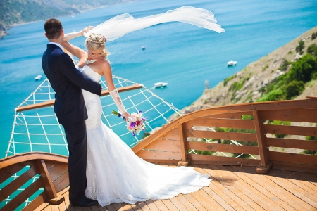 Couple in love bride and groom posing in a restaurant stylized as deck wooden ship on the background of the bay with beautiful cliffs  Enjoying a love and happiness on their wedding day in the summer
