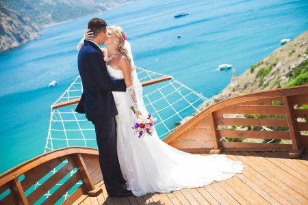Couple in love bride and groom posing in a restaurant stylized as deck wooden ship on the background of the bay with beautiful cliffs  Enjoying a love and happiness on their wedding day in the summer Imagens - 16330276