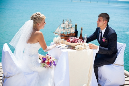 Schönes Paar in der Liebe, die Braut und Bräutigam posiert auf der Brücke am Meer an der Hochzeitstafel mit exotischen Flaschen und Holzmodell Schiff dekoriert Genießen Sie einen Moment des Glücks und der Liebe Standard-Bild - 16330262