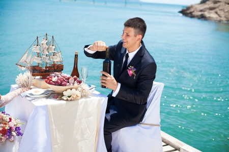 Beautiful couple in love the bride and groom posing on the bridge at the sea at the wedding table decorated with exotic bottles and wooden model ship  Enjoy a moment of happiness and love  photo