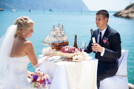 Beautiful couple in love the bride and groom posing on the bridge at the sea at the wedding table decorated with exotic bottles and wooden model ship  Enjoy a moment of happiness and love Stock Photo - 16330242