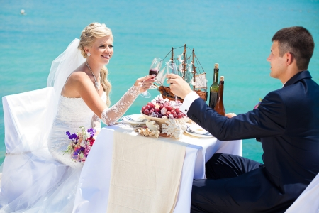 Beautiful couple in love the bride and groom posing on the bridge at the sea at the wedding table decorated with exotic bottles and wooden model ship  Enjoy a moment of happiness and love  Stock Photo - 16330250