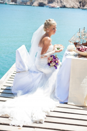 Beautiful bride posing on the bridge at the sea at the wedding table  Enjoy a moment of happiness and love in her wedding day in the summer  photo