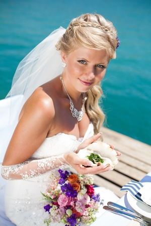 Beautiful bride posing on the bridge at the sea at the wedding table  Enjoy a moment of happiness and love in her wedding day in the summer