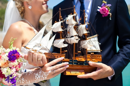 Beautiful couple in love the bride and groom posing on the bridge at the sea at the wedding table decorated with exotic bottles and wooden model ship  Enjoy a moment of happiness and love Stock Photo - 16330275