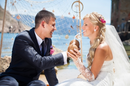 Beautiful blonde bride and groom poses on a background of the sea wedding decorations - net and seashells, sipping a summer cocktail in coconut  Wedding day in summer, on the shore of the blue sea  photo