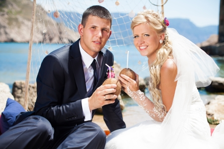 Beautiful blonde bride and groom poses on a background of the sea wedding decorations - net and seashells, sipping a summer cocktail in coconut  Wedding day in summer, on the shore of the blue sea  Stock Photo