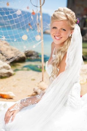 Beautiful blonde bride in a wedding dress poses on a background of the sea wedding decorations - net and seashells  Enjoying her wedding day in summer, on the shore of the blue sea  photo