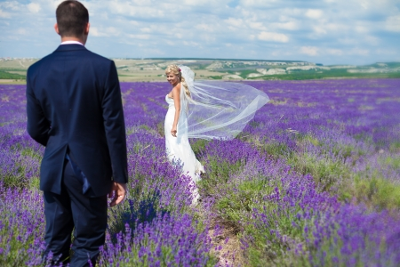 A young couple in love bride and groom, wedding day in summer  Enjoy a moment of happiness and love in a lavender field  Bride in a luxurious wedding dress on a background bright blue sky with clouds  photo