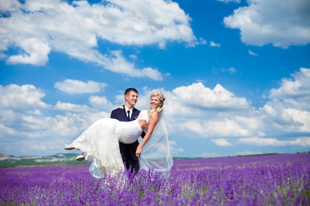 A young couple in love bride and groom, wedding day in summer  Enjoy a moment of happiness and love in a lavender field  Bride in a luxurious wedding dress on a background bright blue sky with clouds