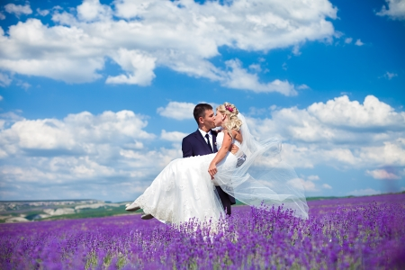 A young couple in love bride and groom, wedding day in summer  Enjoy a moment of happiness and love in a lavender field  Bride in a luxurious wedding dress on a background bright blue sky with clouds  Stock Photo - 16333669