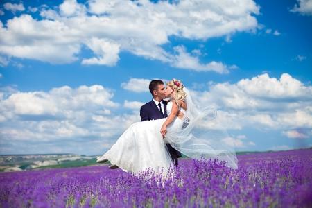 vőlegény: Egy fiatal szerelmes pár menyasszony és a vőlegény, esküvő napján nyáron Élvezze a pillanatot a boldogság és a szeretet a levendula területen menyasszony egy fényűző esküvői ruha a háttérben ragyogó kék ég a felhők