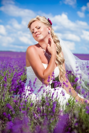 Young and beautiful bride in love, wedding day in summer  Enjoy a moment of happiness and love in a lavender field  In a luxurious wedding dress on a background bright blue sky with clouds  Stock Photo
