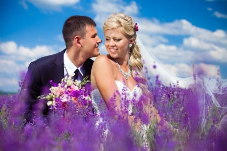Ein junges Paar in der Liebe Braut und Bräutigam, Genießen Hochzeit im Sommer einen Moment des Glücks und der Liebe in einem Lavendelfeld Braut in einem luxuriösen Hochzeitskleid auf einem Hintergrund strahlend blauer Himmel mit Wolken Standard-Bild - 16333677