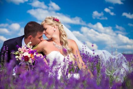 A young couple in love bride and groom, wedding day in summer  Enjoy a moment of happiness and love in a lavender field  Bride in a luxurious wedding dress on a background bright blue sky with clouds Imagens - 16333603