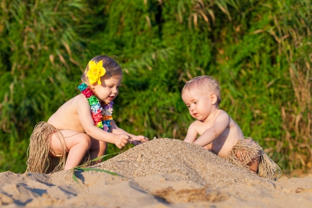 Young children are a boy and girl playing in the sand by the sea in comic costumes - skirts the wild tribes  Summer  Stock Photo - 16333670