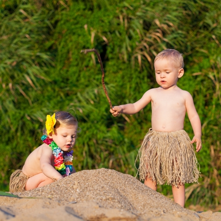 Young children are a boy and girl playing in the sand by the sea in comic costumes - skirts the wild tribes  Summer  Stock Photo - 16333543
