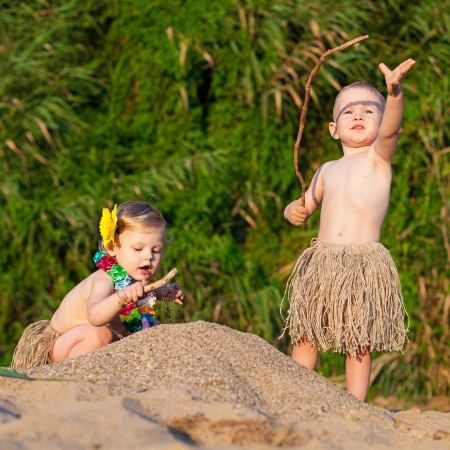 Young children are a boy and girl playing in the sand by the sea in comic costumes - skirts the wild tribes  Summer Young children are a boy and girl playing in the sand by the sea in comic costumes - skirts the wild tribes  Summer  Stock Photo - 16333545