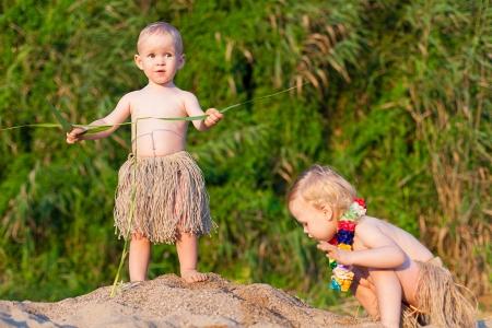 Los niños pequeños son un niño y una niña jugando en la arena junto al mar en trajes cómicos - bordea el verano tribus salvajes Foto de archivo - 16333479