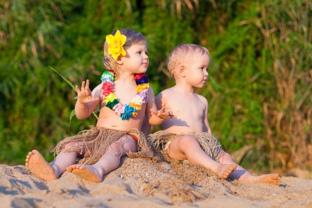 Young children are a boy and girl playing in the sand by the sea in comic costumes - skirts the wild tribes  Summer  Stock Photo - 16333547
