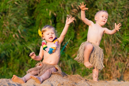 Young children are a boy and girl playing in the sand by the sea in comic costumes - skirts the wild tribes  Summer  Stock Photo - 16333480