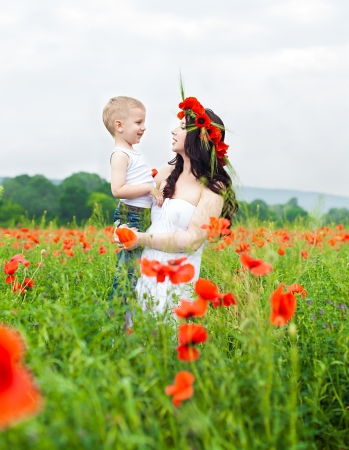Beautiful young family mother and her son walking on the poppy field in summer Stock Photo - 16333558